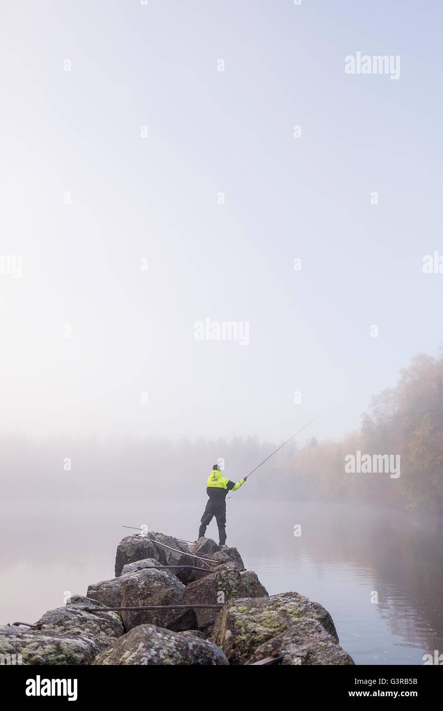 Sweden, Vastmanland, Bergslagen, Torrvarpen, Young man fishing in lake on foggy day - Stock Image