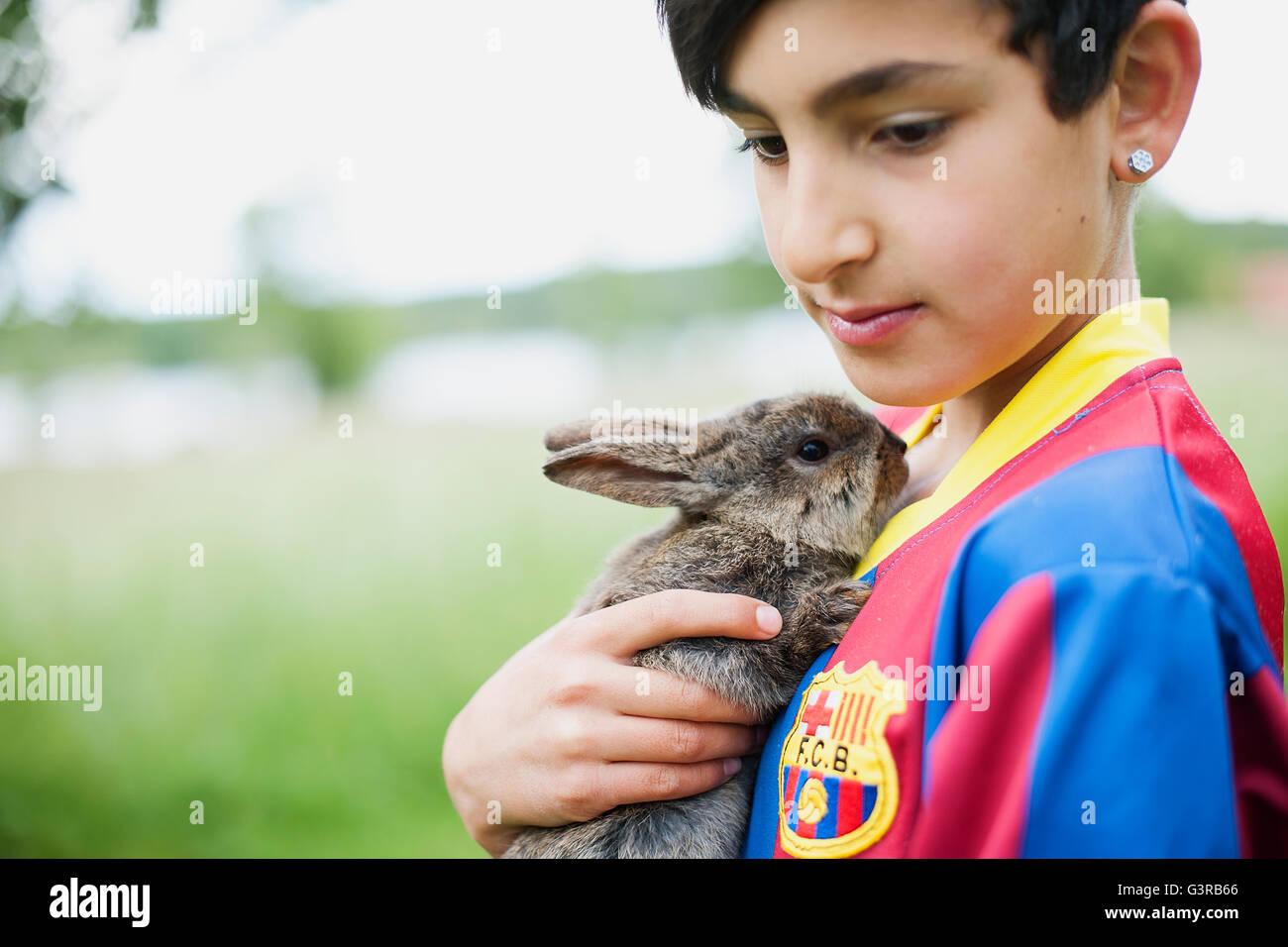 Sweden, Varmland, Filipstad, Gasborn, Horrsjon, Boy (10-11) in sport jersey holding rabbit - Stock Image