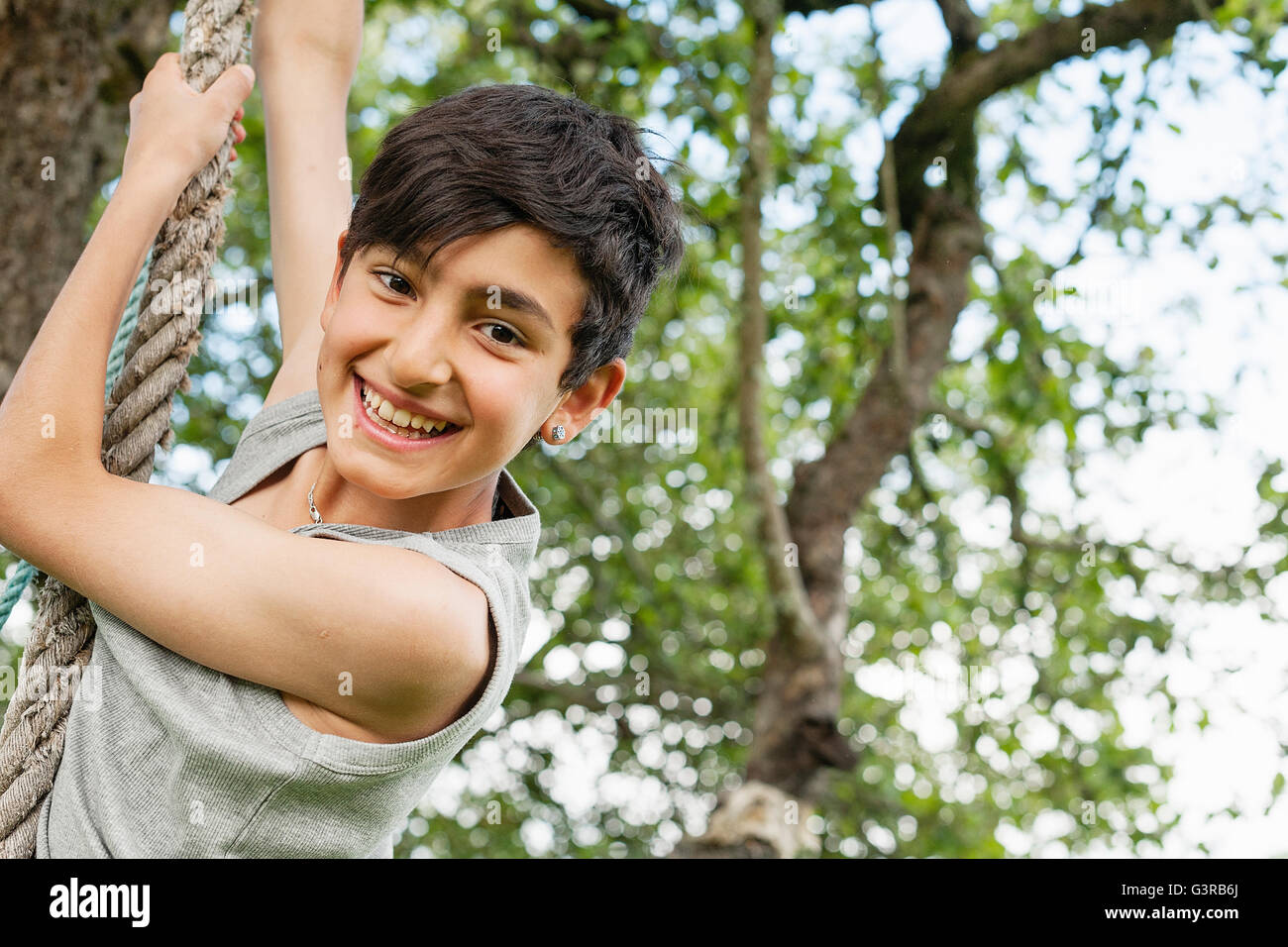 Sweden, Varmland, Filipstad, Gasborn, Horrsjon, Boy (10-11) playing on rope - Stock Image
