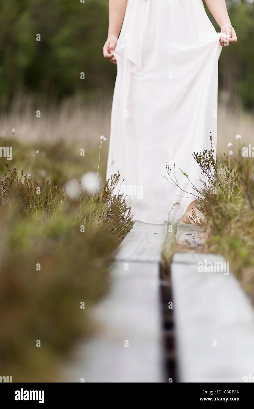Sweden, Vastmanland, Teenage girl (16-17) in white dress standing on overpass in meadow - Stock Image