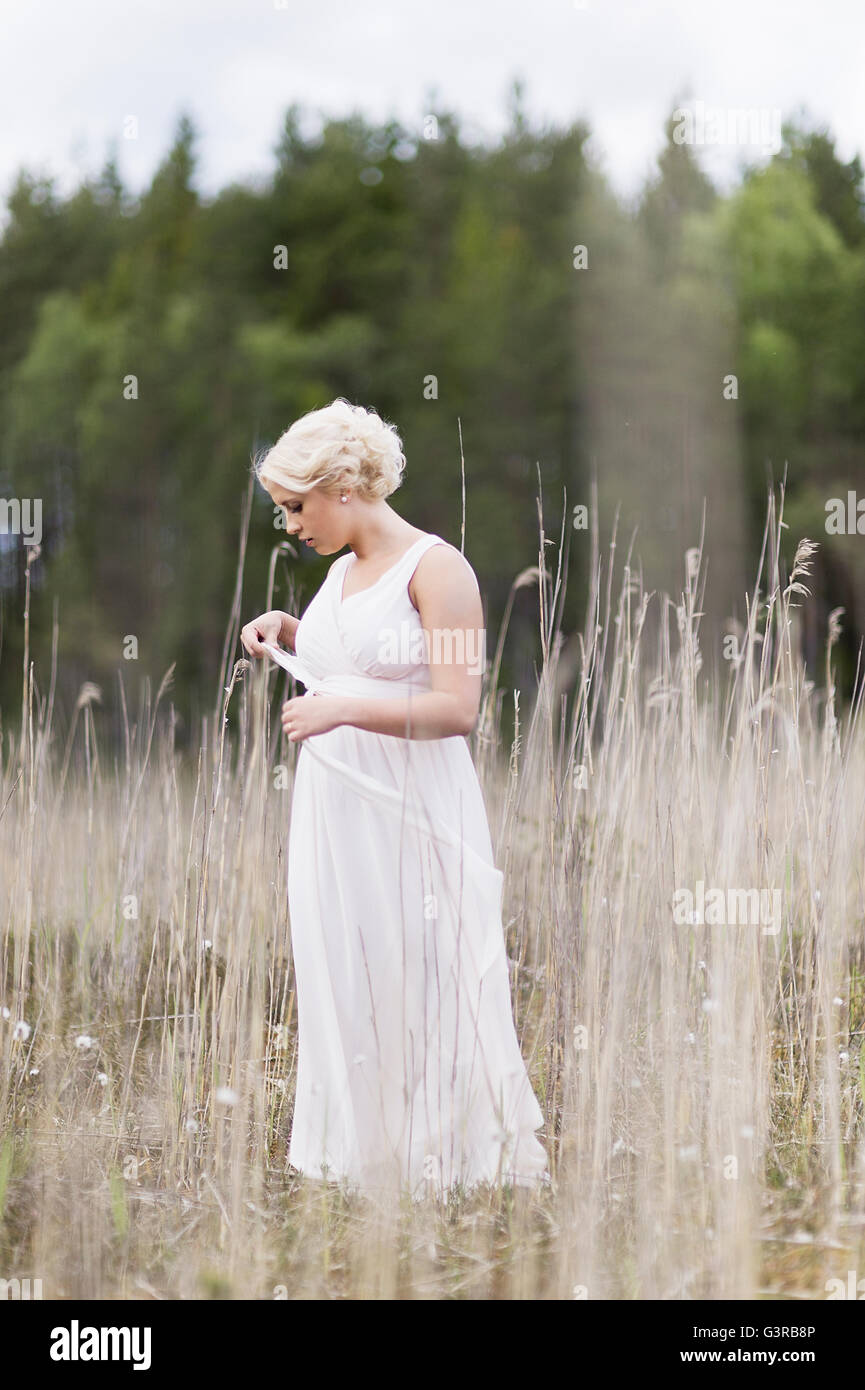 Sweden, Vastmanland, Teenage girl (16-17) in white dress standing in meadow among dried plants - Stock Image