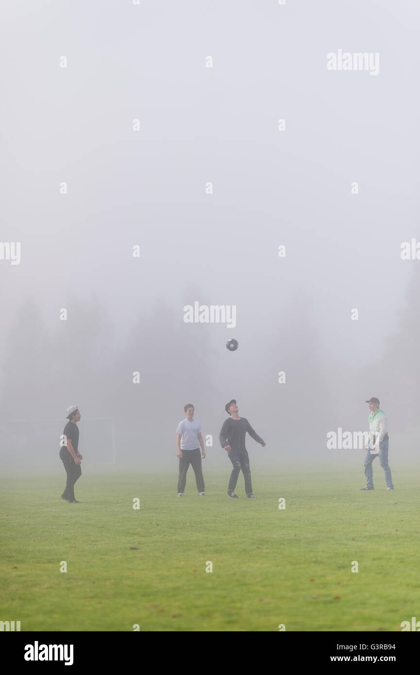 Sweden, Vastmanland, Teenage boys (14-15, 16-17) playing soccer in fog - Stock Image