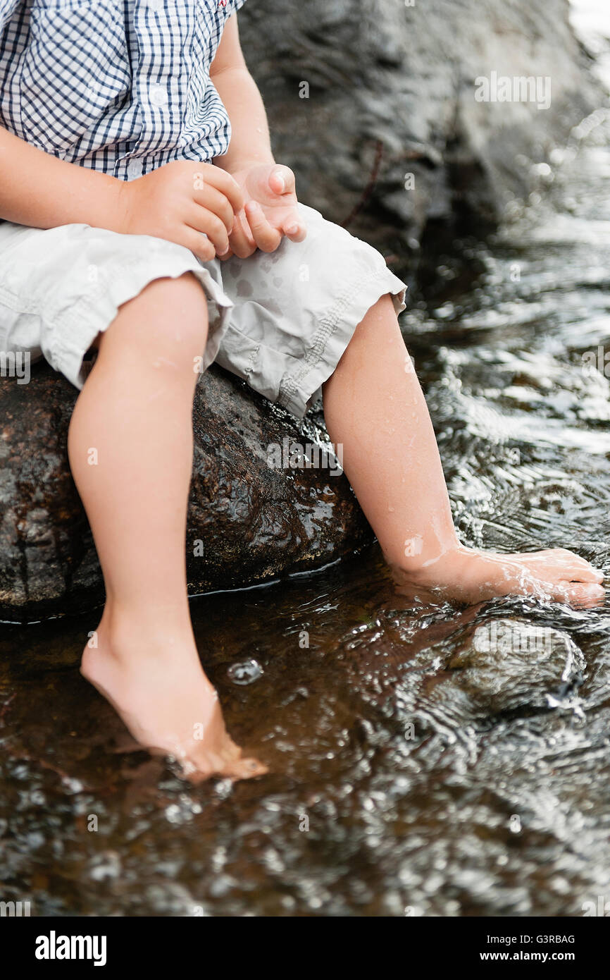 Sweden, Vastmanland, Baby boy (18-23 months) dipping feet in water - Stock Image