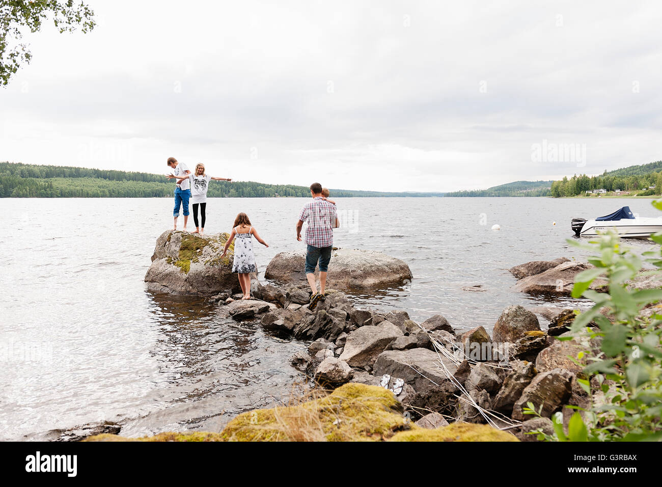 Sweden, Vastmanland, Bergslagen, Hallefors, Nygard, Family with four children standing on rocks - Stock Image