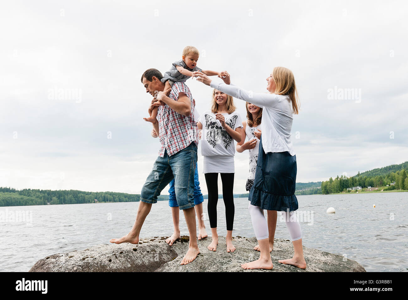 Sweden, Vastmanland, Bergslagen, Hallefors, Nygard, Family with four children standing on rock - Stock Image