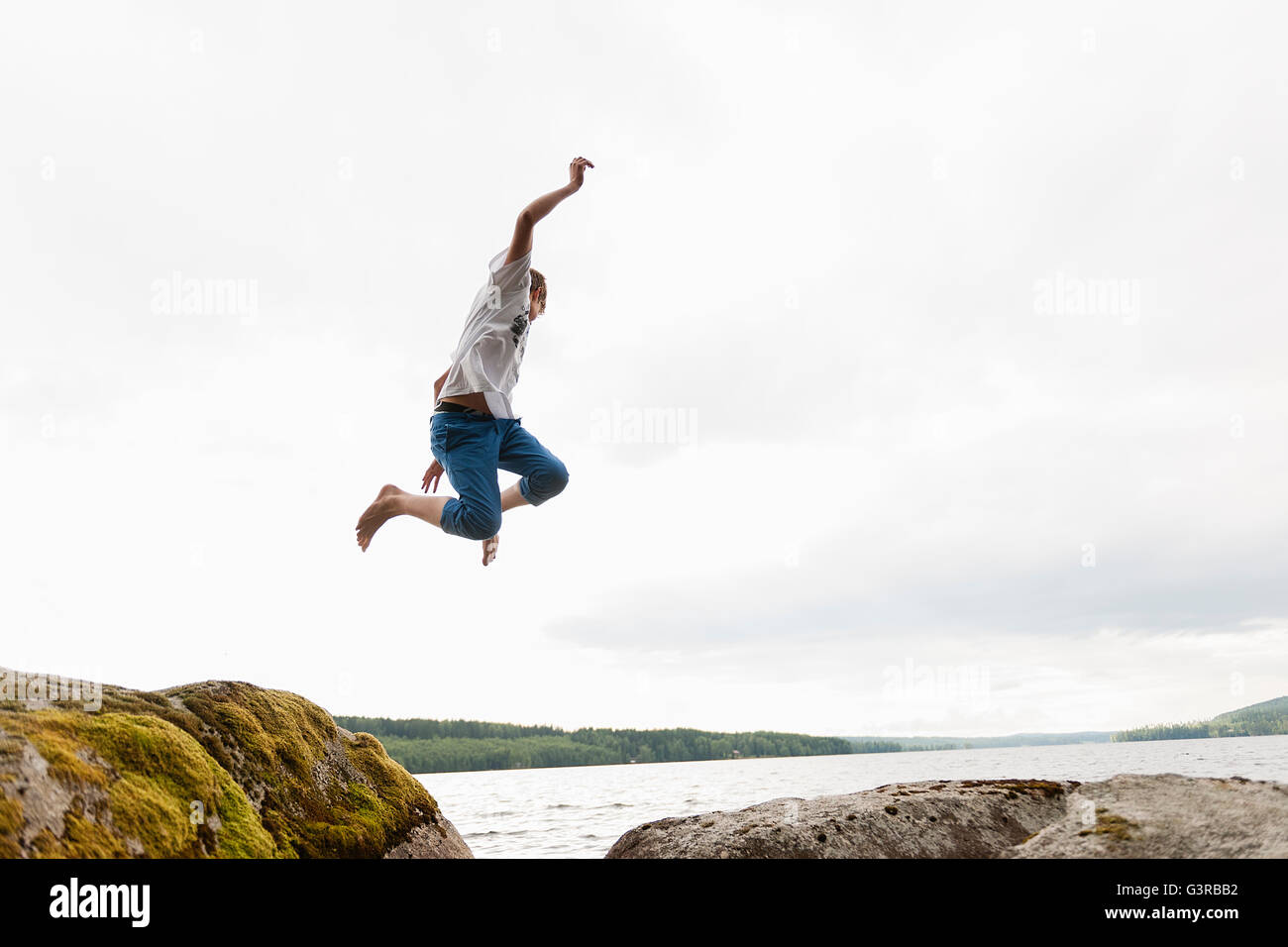 Sweden, Vastmanland, Bergslagen, Hallefors, Nygard, Teenage boy (14-15) jumping from rocks - Stock Image