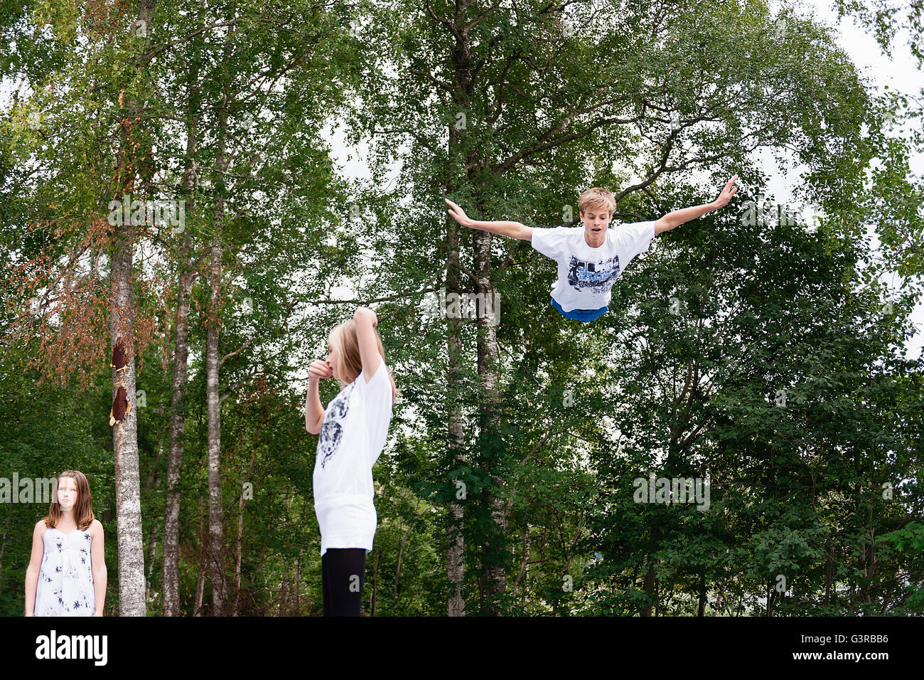 Sweden, Vastmanland, Bergslagen, Hallefors, Nygard, Children (10-11, 12-13, 14-15) against green trees - Stock Image