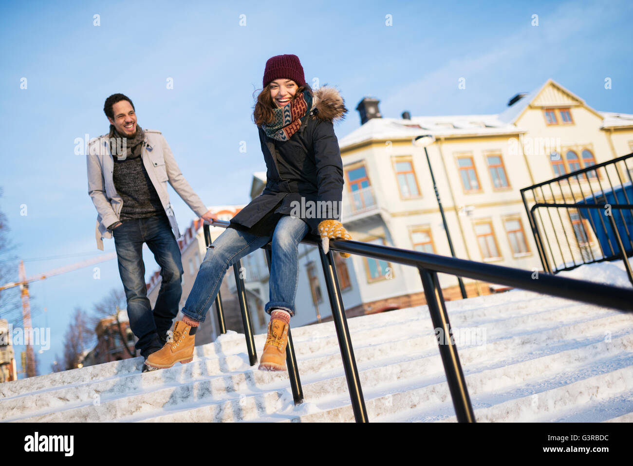 Sweden, Vasterbotten, Umea, Man watching young woman sliding on railing - Stock Image