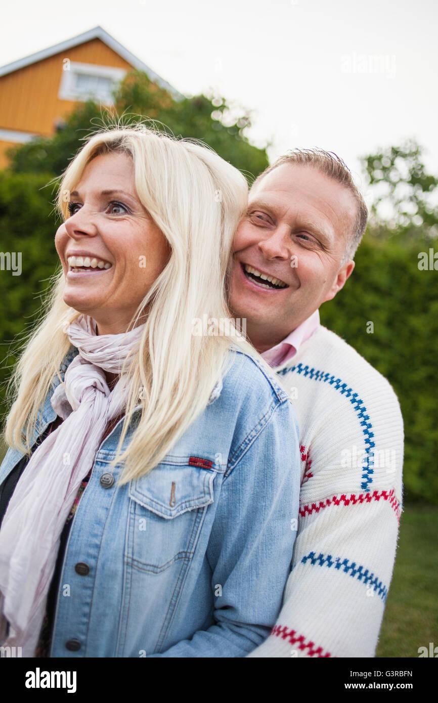 Sweden, Blekinge, Smiling couple embracing - Stock Image