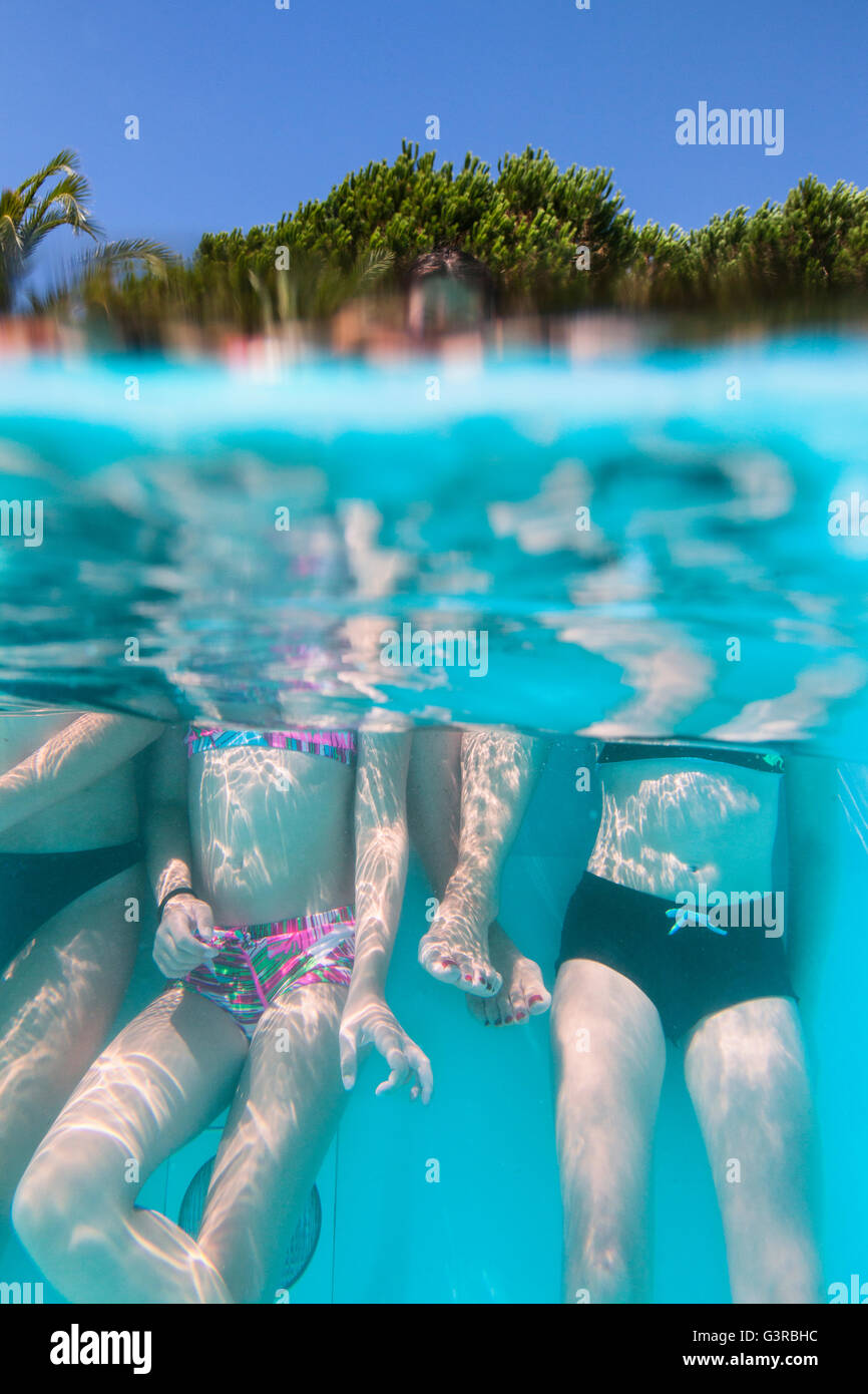 Italy, Sardinia, Alghero, Mother with children (14-15, 16-17) at swimming pool - Stock Image