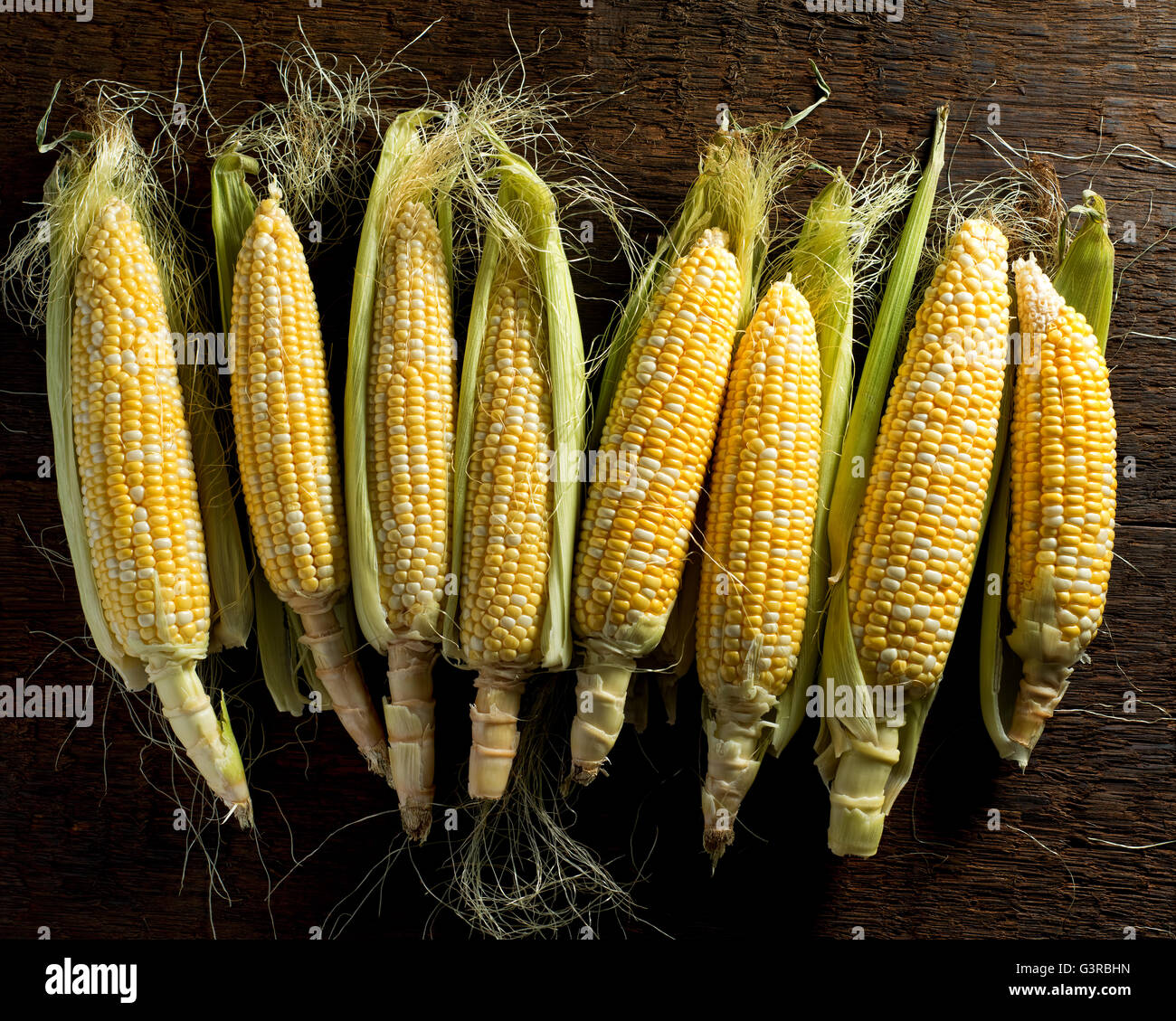 Fresh local organic corn on the cob against a rustic harvest table background. Stock Photo