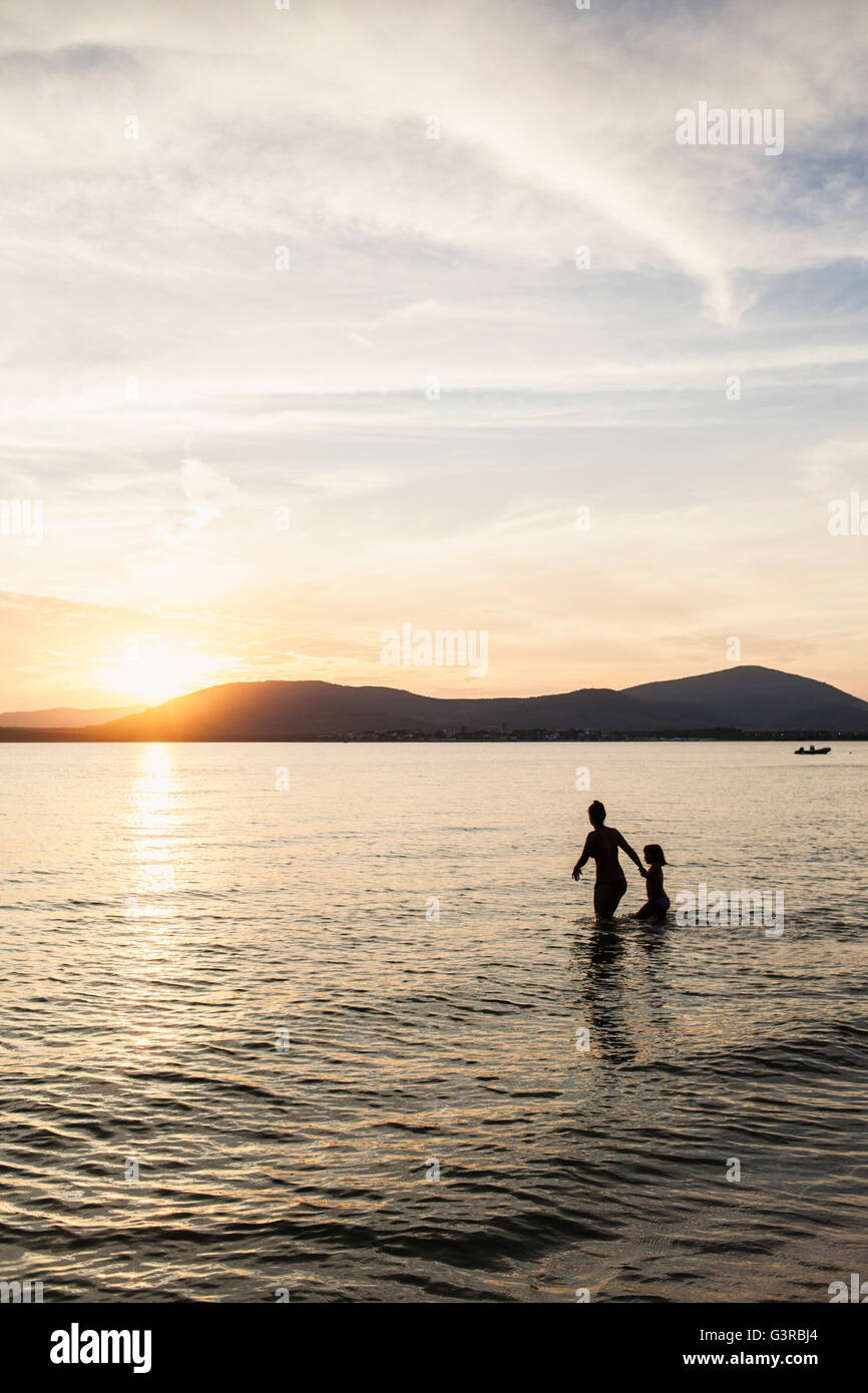 Italy, Sardinia, Alghero, Mother and daughter wading in sea at sunset - Stock Image