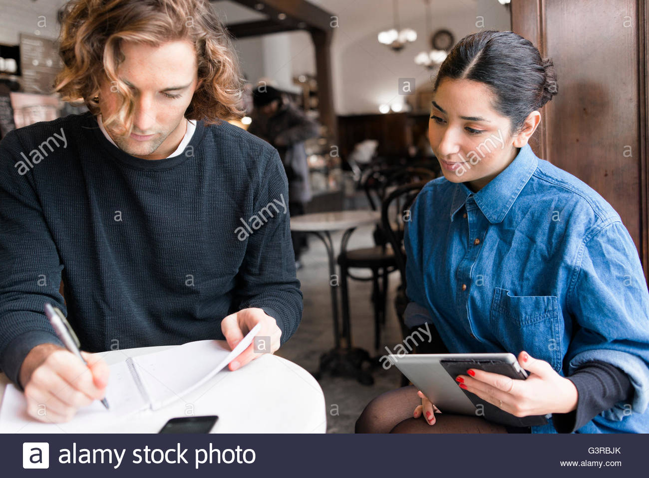 Sweden, Young people working in cafe - Stock Image