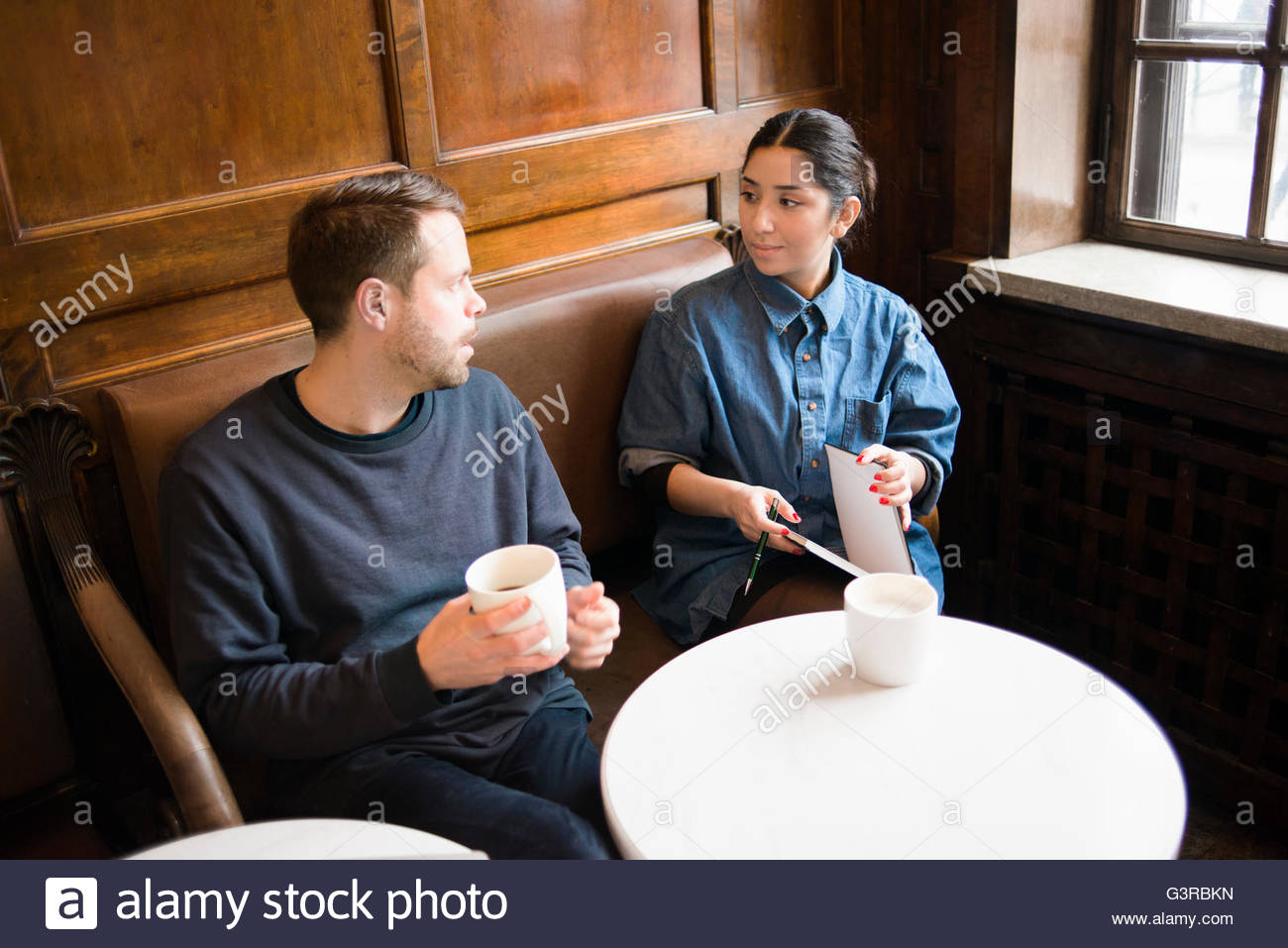Sweden, Young people talking in cafe - Stock Image