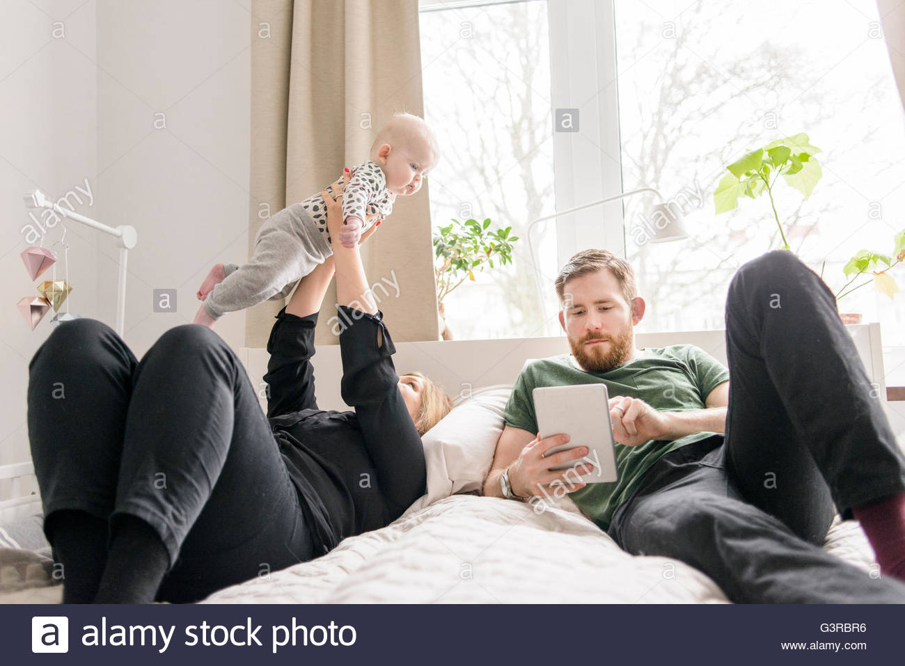 Sweden, Family with baby boy (0-1 months) relaxing in bed - Stock Image