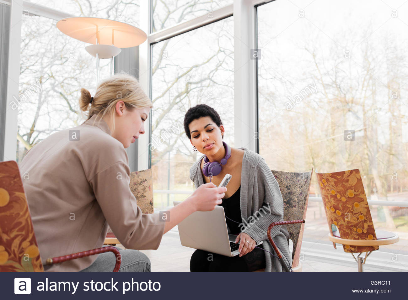 Sweden, Two women using smartphone - Stock Image
