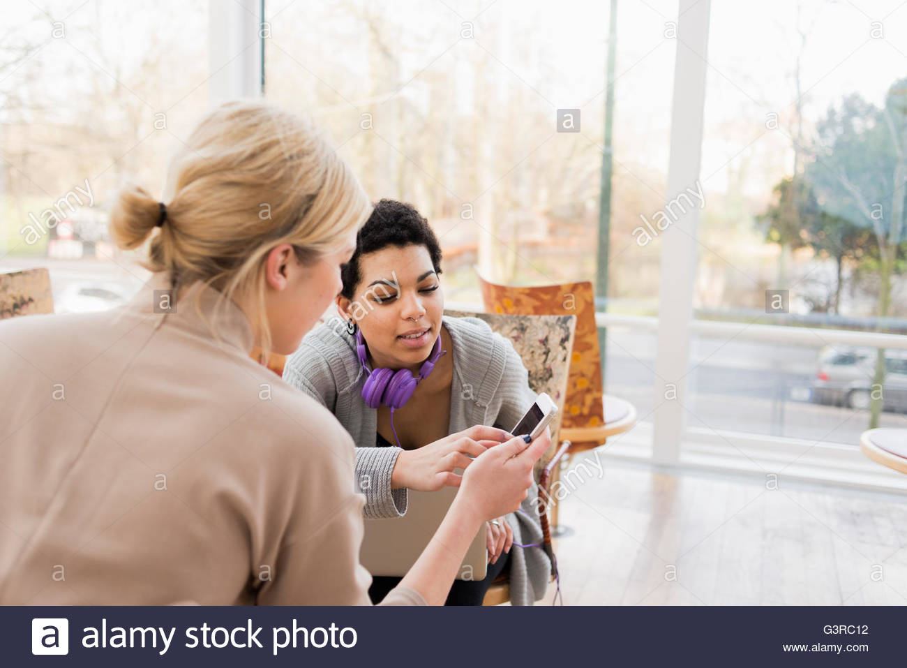 Sweden, Two young women looking at smartphone - Stock Image