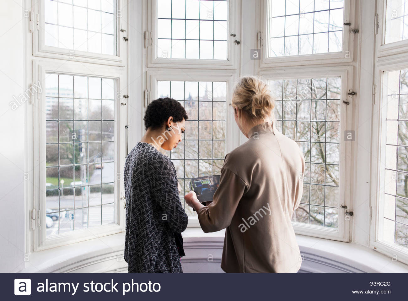 Sweden, Two women talking and reading book - Stock Image