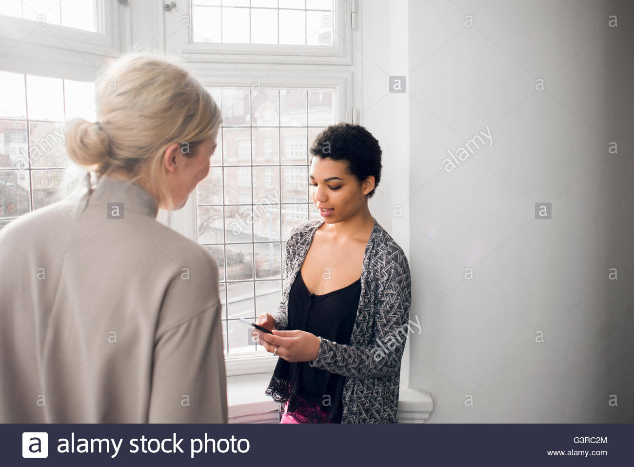 Sweden, Two young women talking - Stock Image