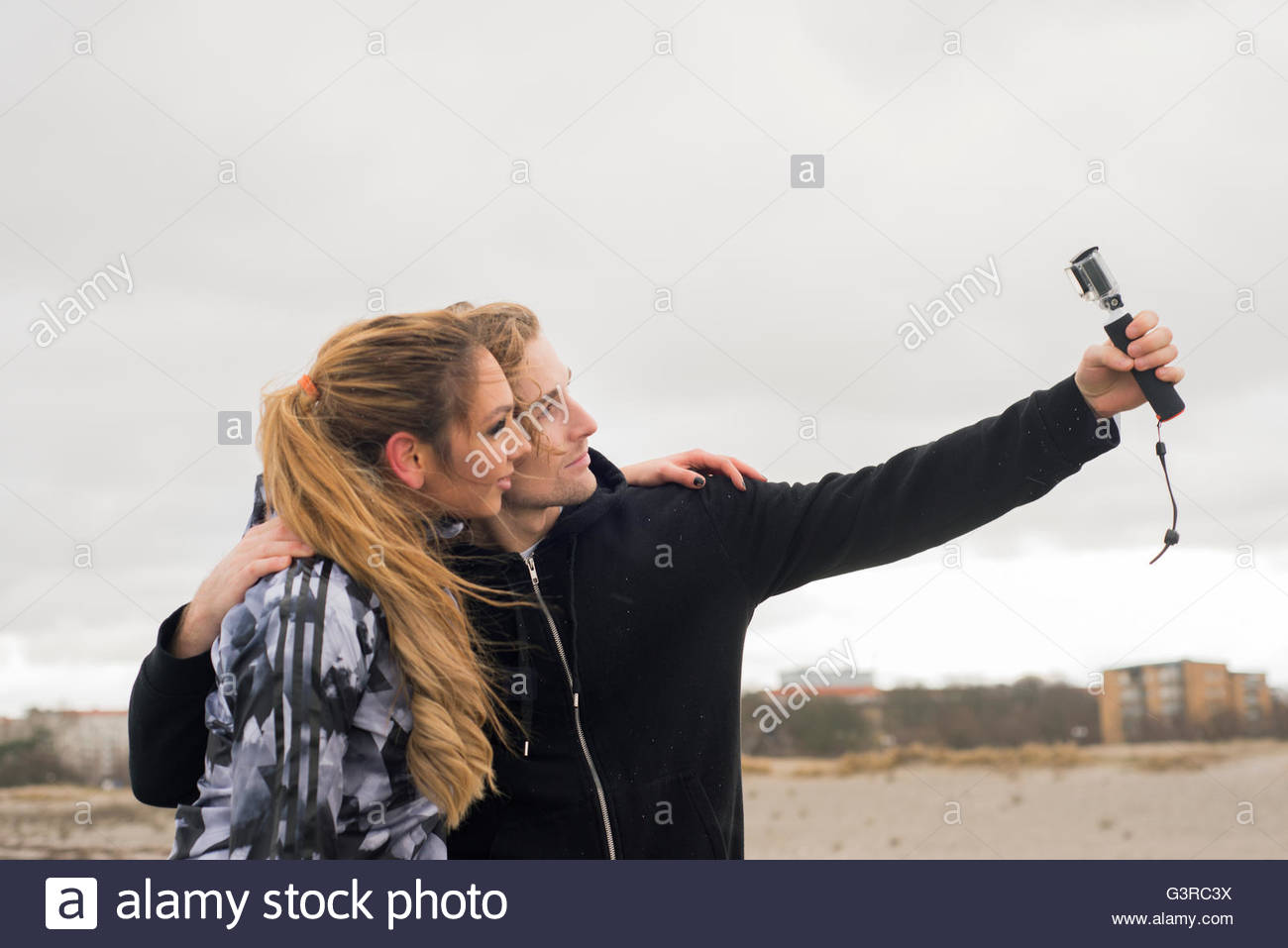 Sweden, Skane, Malmo, Young couple taking selfie on beach - Stock Image