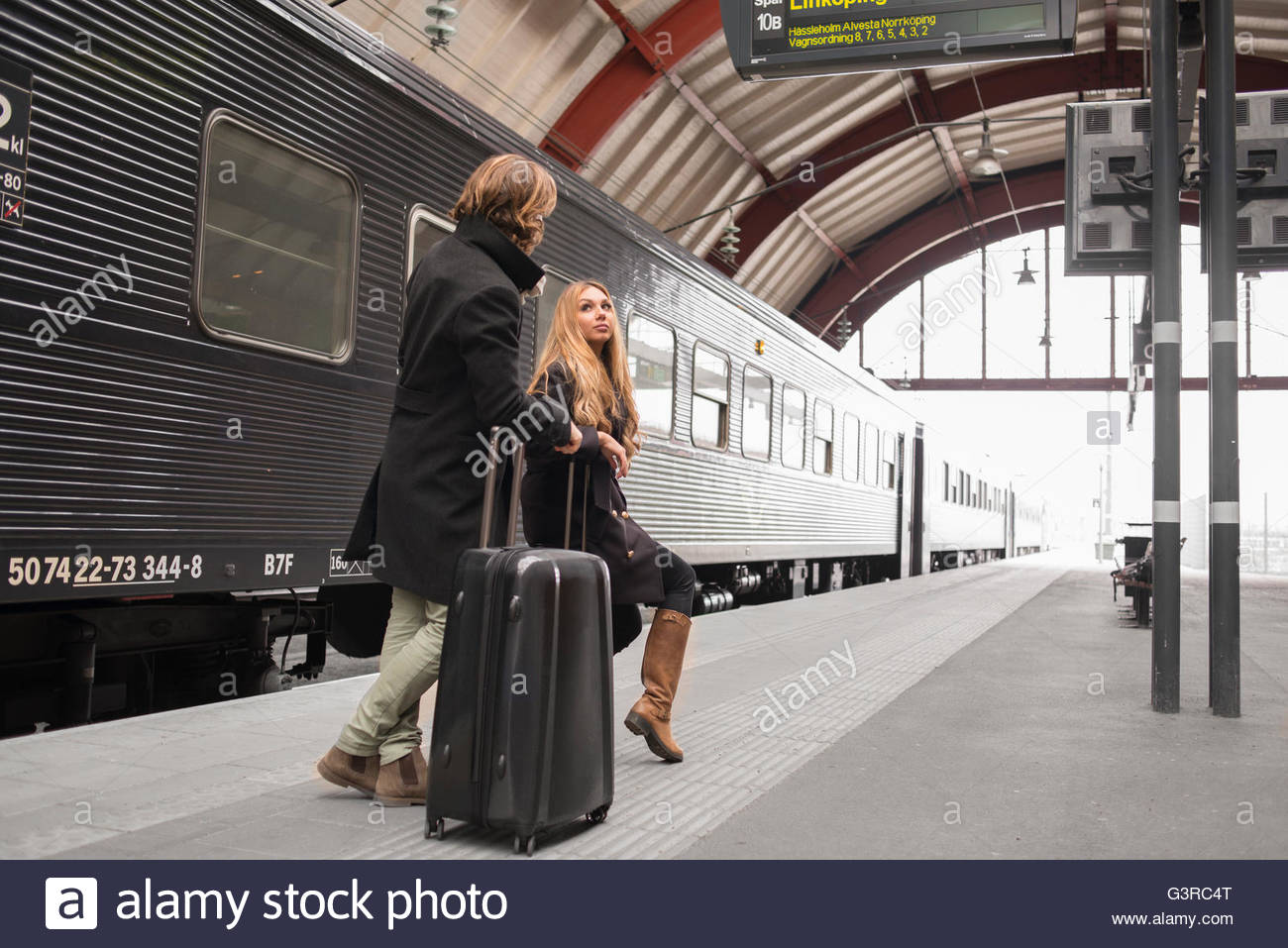 Sweden, Skane, Malmo, Young couple talking at railroad station - Stock Image