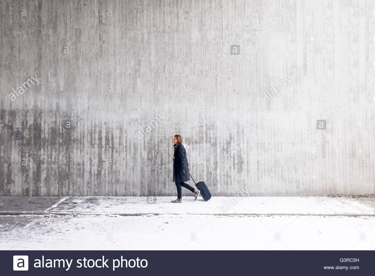 Sweden, Man with wheeled luggage in front of wall - Stock Image