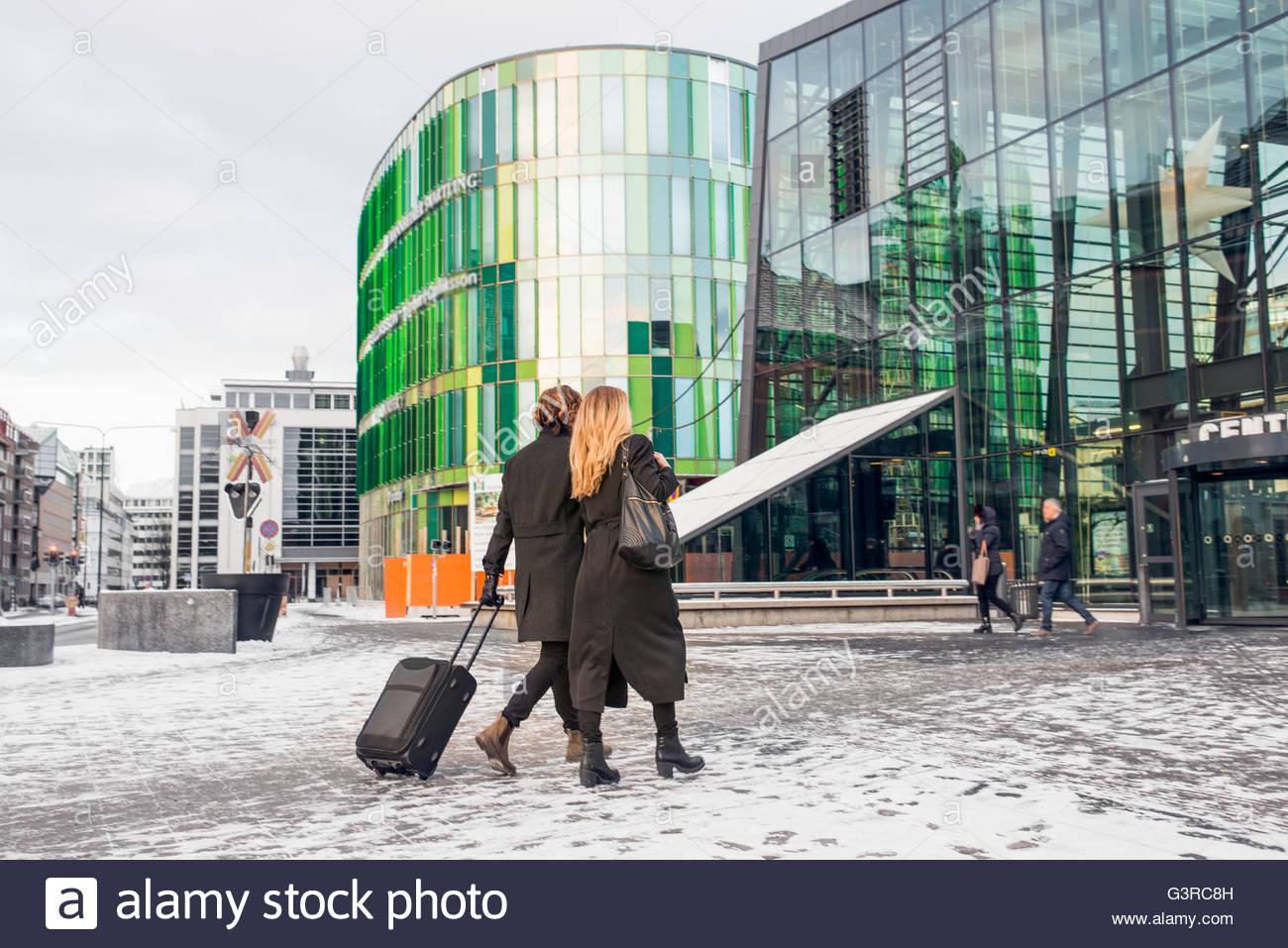 Sweden, Skane, Malmo, Couple with wheeled luggage walking towards modern building - Stock Image