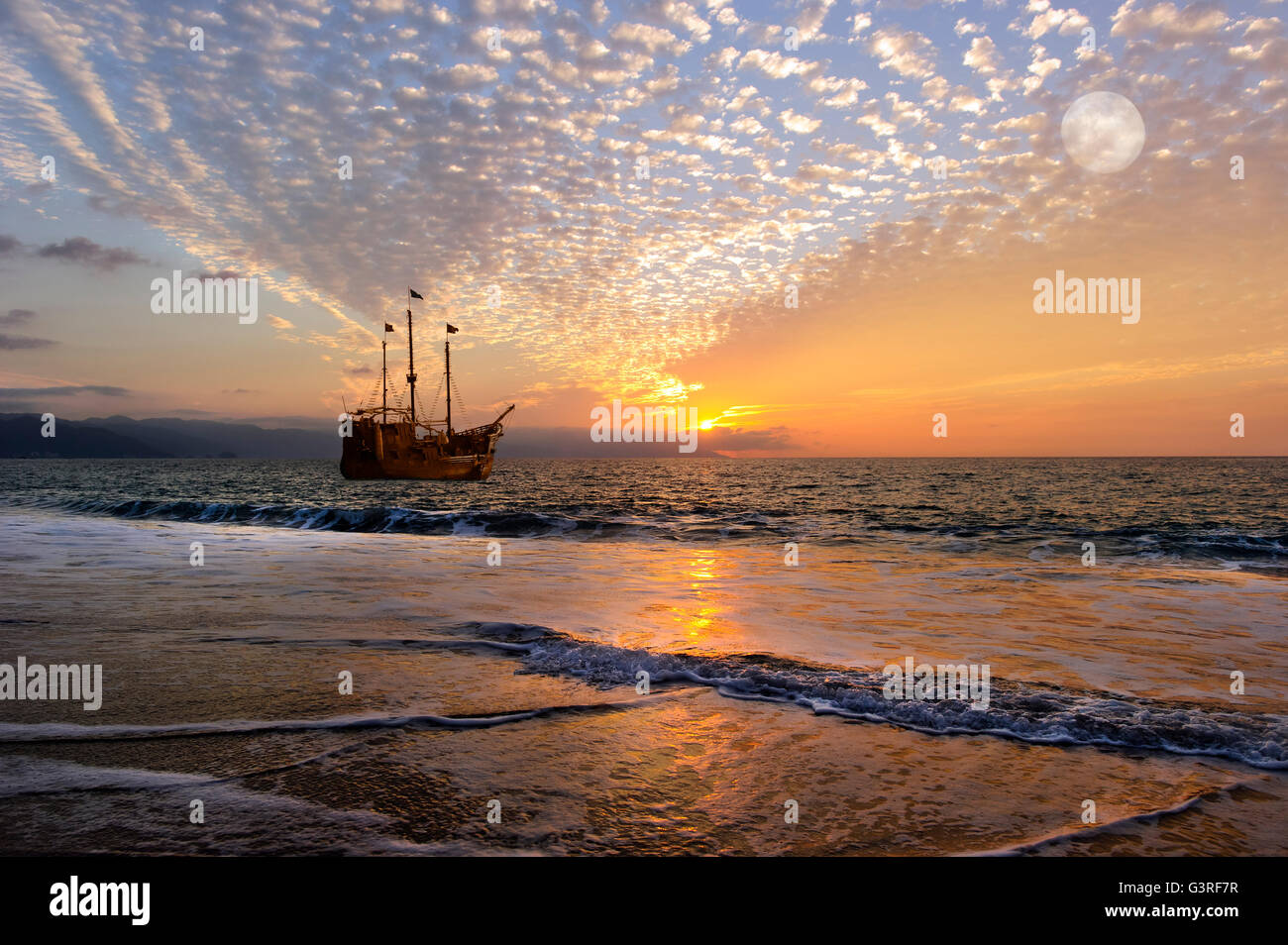 Pirate ship fantasy is an old wooden pirate ship with full flags as the sun sets on the ocean and the moon rises Stock Photo