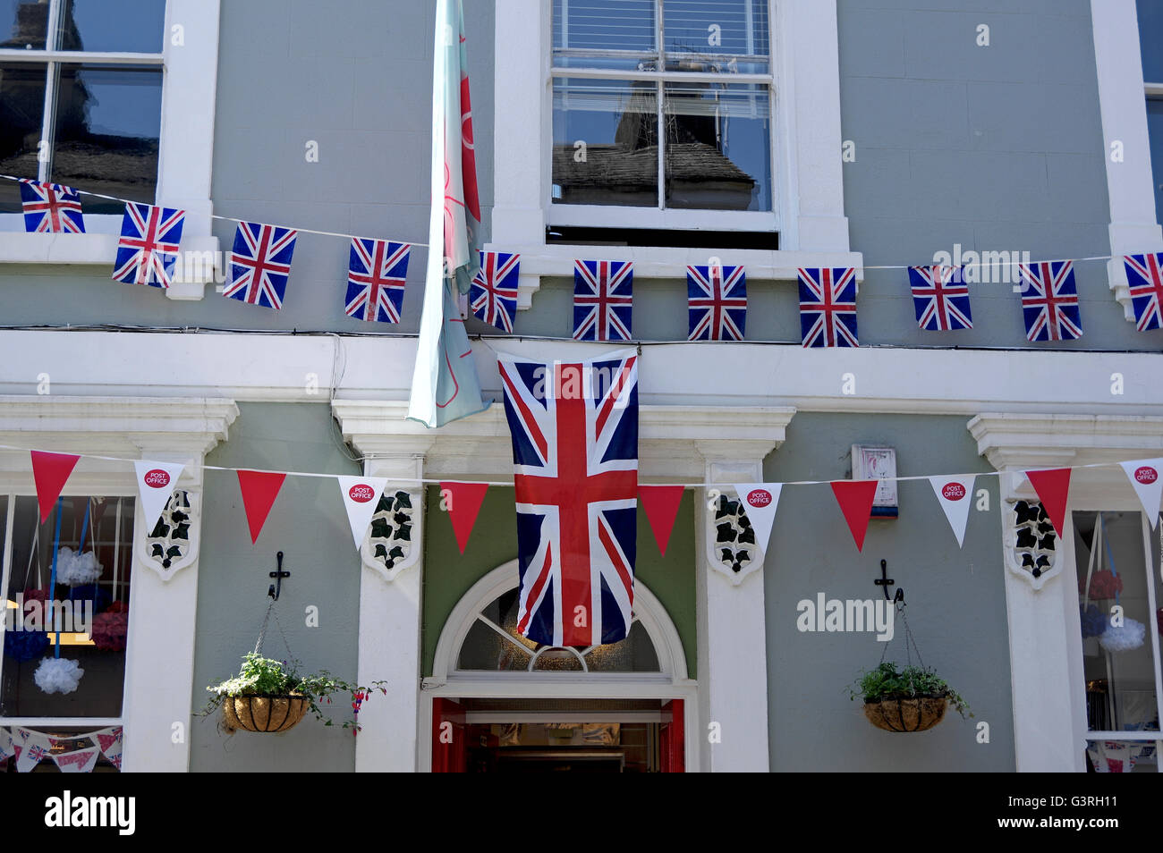 Bunting hanging outside the Post Office in Ashburton in preparation for the Queen's 90th birthday celebrations. - Stock Image