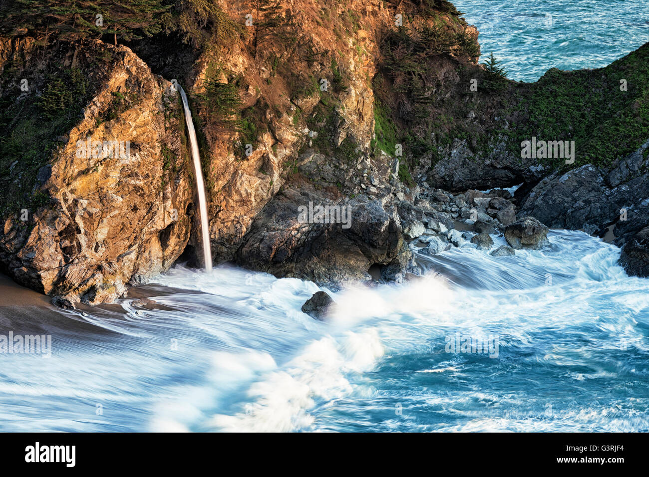 Evening light bathes Julia Pfeiffer Burns State Park as McWay Falls pours into the Pacific Ocean along California's - Stock Image
