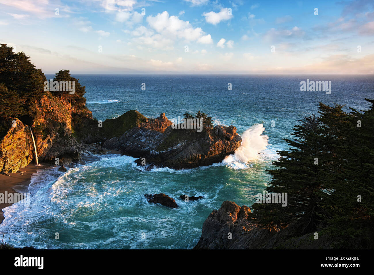 Last light reveals exploding waves at California's Julia Pfeiffer Burns State Park as McWay Falls pours into the - Stock Image