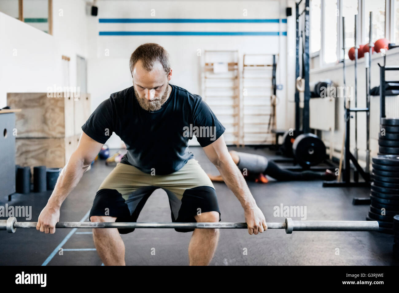 Germany, Young man weightlifting - Stock Image