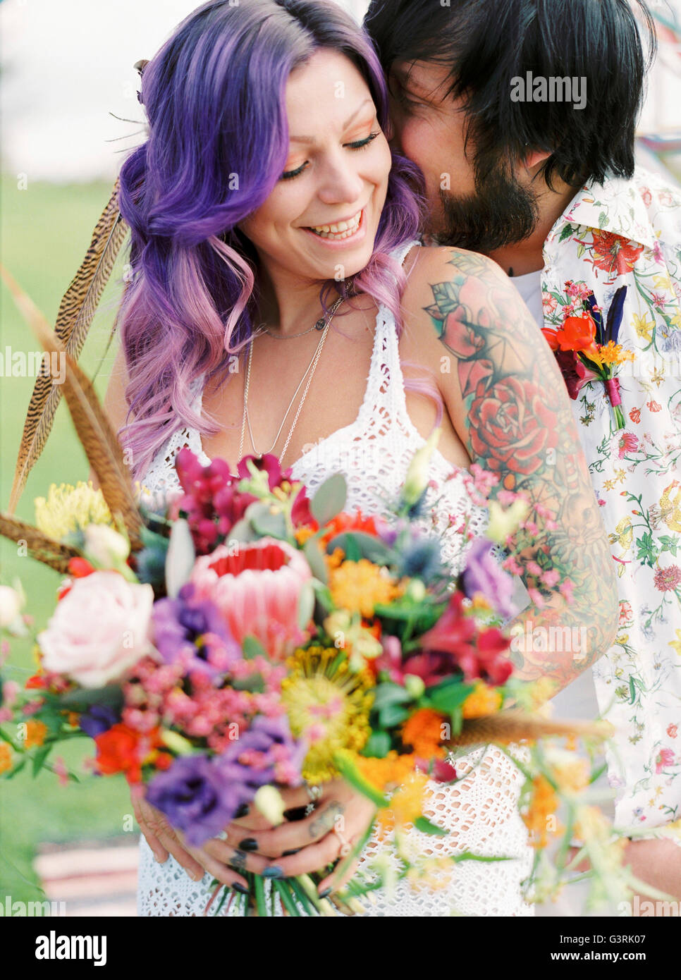 Sweden, Groom kissing bride at hippie wedding - Stock Image
