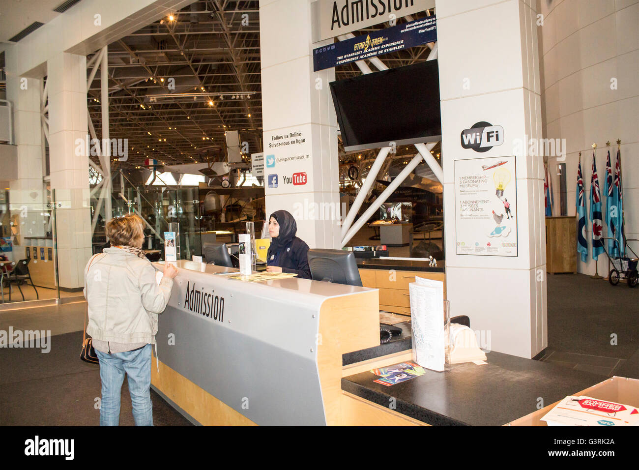 Muslim woman talking with visitor at the admission desk at the Canadian Aviation and Space Museum in Ottawa Ontario, - Stock Image