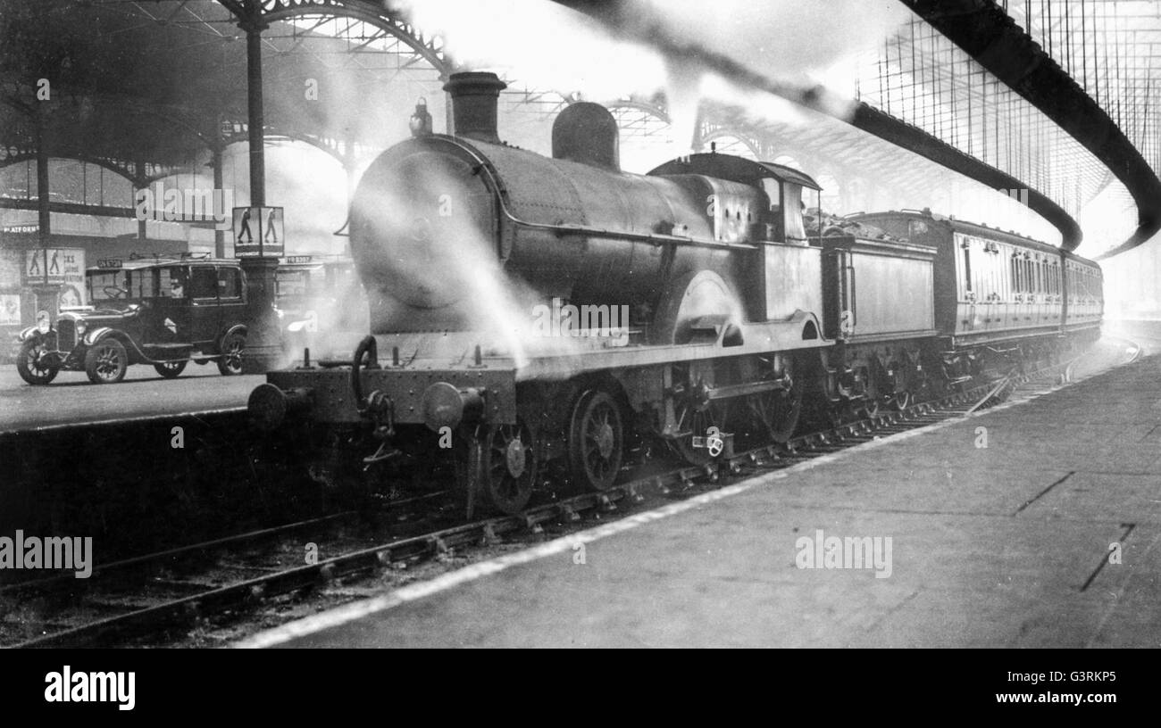 A LNWR Precursor 4-4-0 arrives at Euston with an outer suburban service possibly from Bletchley or Rugby. - Stock Image