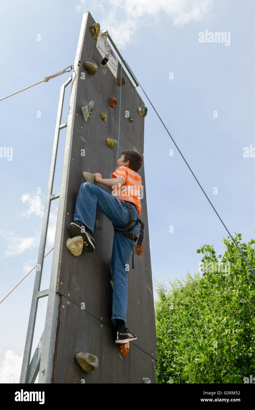 Massagno, Switzerland - 12 June 2016 - Effort of a boy in climbing a wall to reach the top - Stock Image