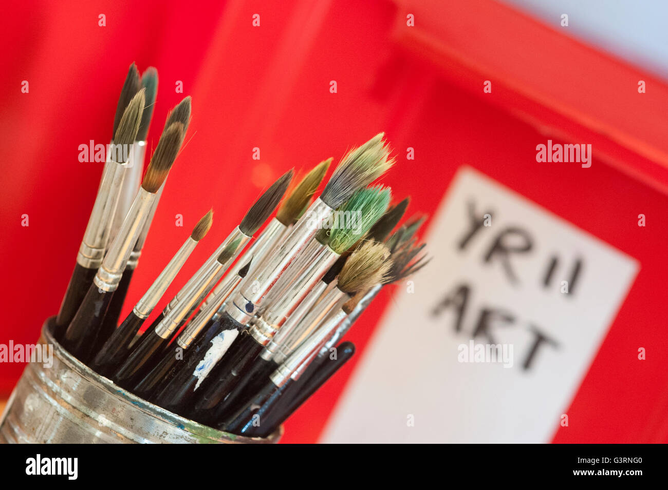 Paint brush pot in a school art department classroom. England. UK - Stock Image