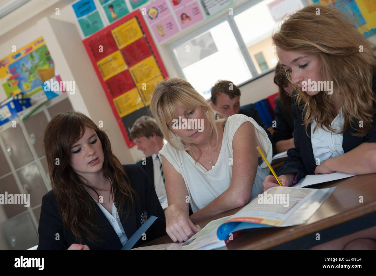 Female teacher in a class of teenagers. England. UK - Stock Image