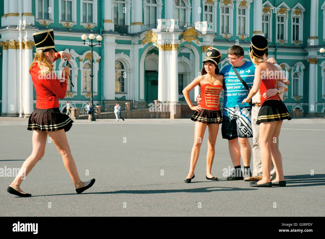 Saint Petersburg Russia. Enterprising young women pose as Palace Guards for tourist photographs in front of the - Stock Image