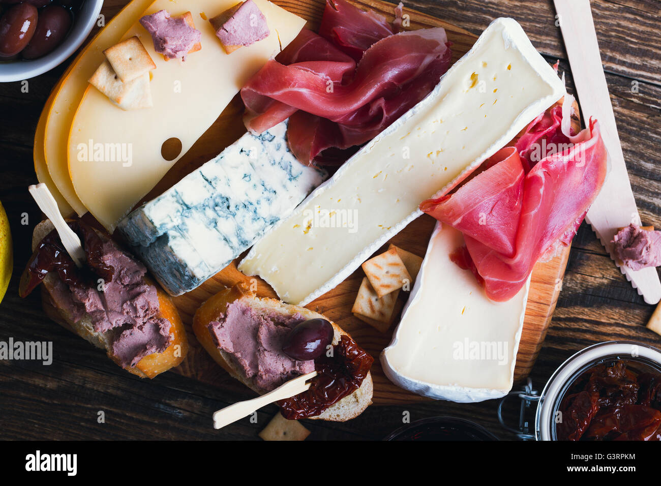 Antipasti platter with different meat and cheese products on  wooden board. Top view - Stock Image