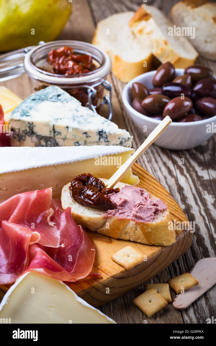 Antipasti platter with different meat and cheese products on  wooden board - Stock Image