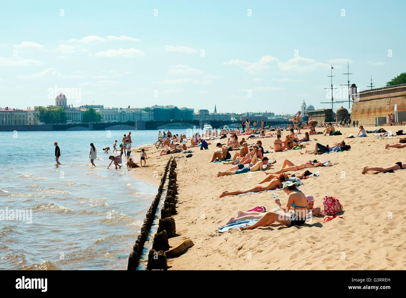 Saint Petersburg Russia. Sunbathing on beach outside the walls of Peter and Paul Fortress on Zayachy Island on the - Stock Image