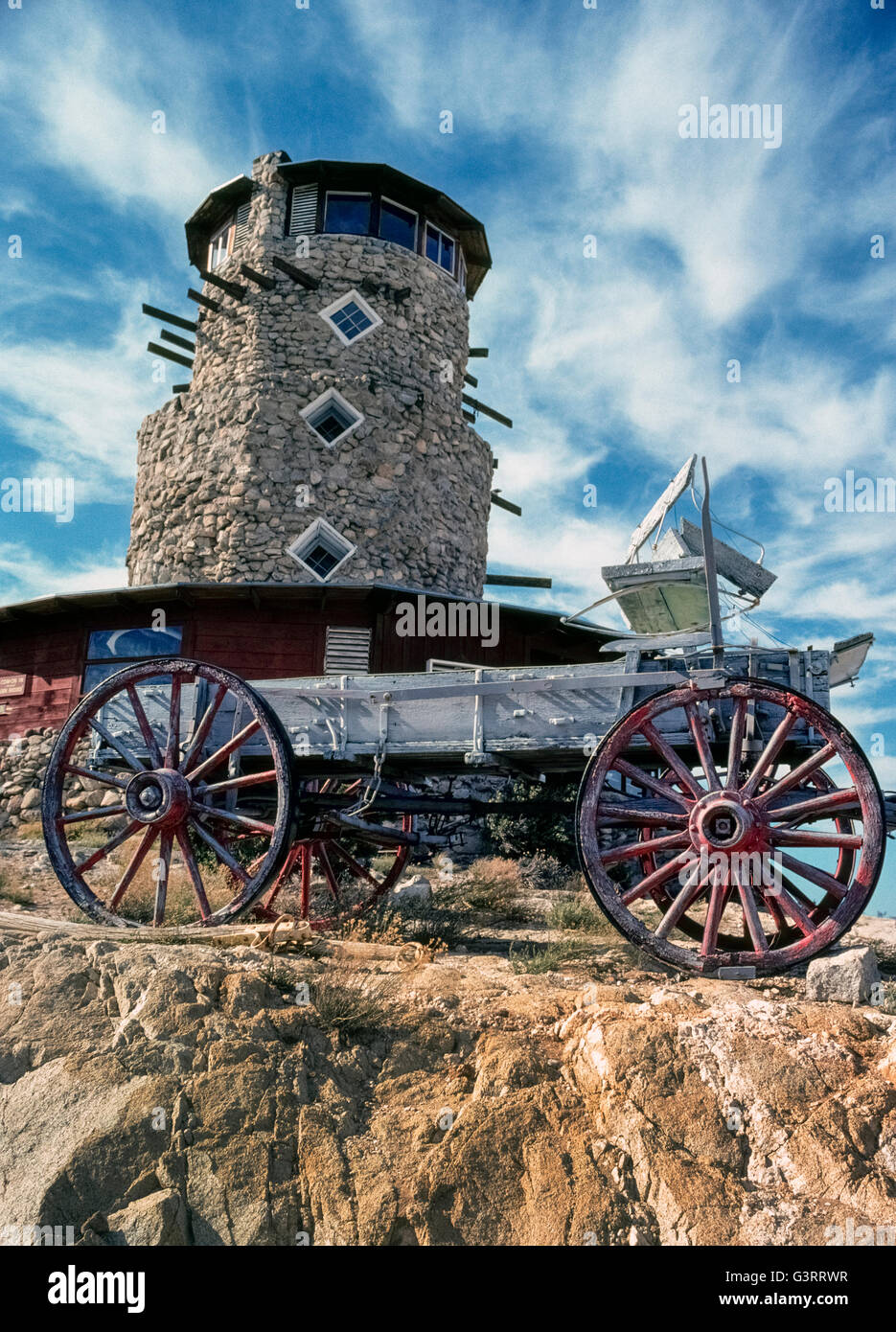 A wagon that is a relic of the Old West sits in front of the Desert View Tower that opened in 1920s as a roadside - Stock Image