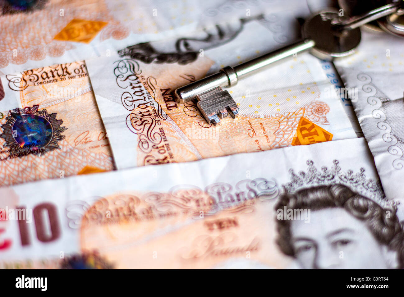 House keys and British pound bank notes depicting cost of moving, rent or mortgages - Stock Image