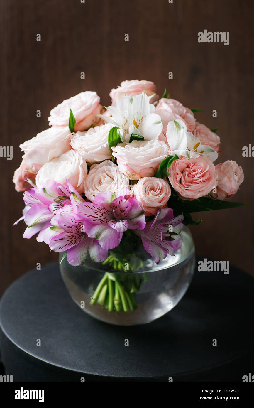 still life. a wooden antique table, glass vase with Mixed bouquet. beautiful flowers Stock Photo