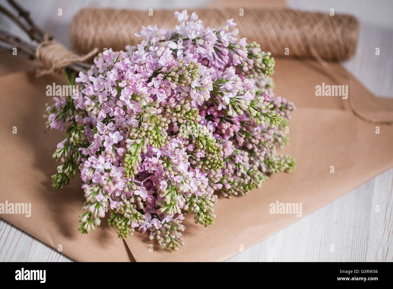 Empty postal envelope and bouquet of lilac flowers on the white wooden background, copy space. Top view. - Stock Image