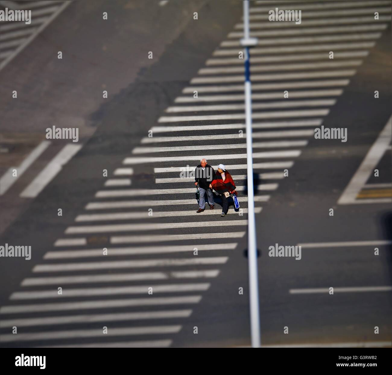 An old Chinese couple crossing the road. - Stock Image