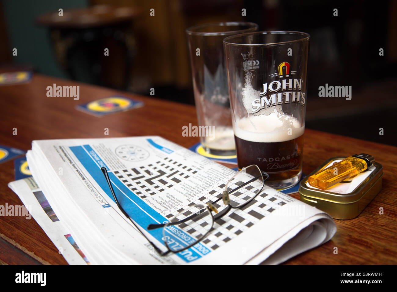 A lunch break view of the days local crossword puzzle with the remains of a pint of beer/ale in an English pub/bar. - Stock Image
