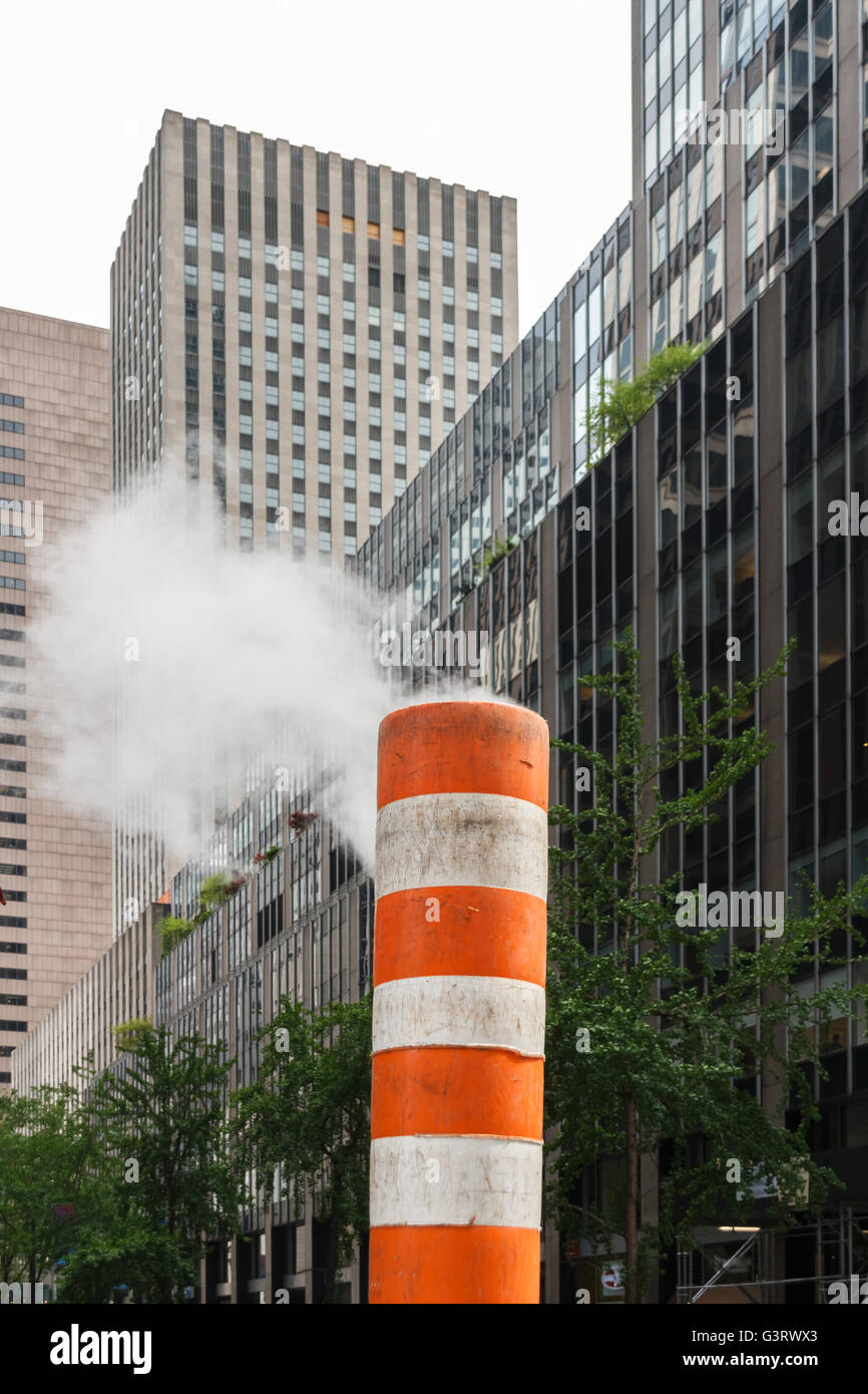Steam rising out of a subway vent in a street of New York City - Stock Image