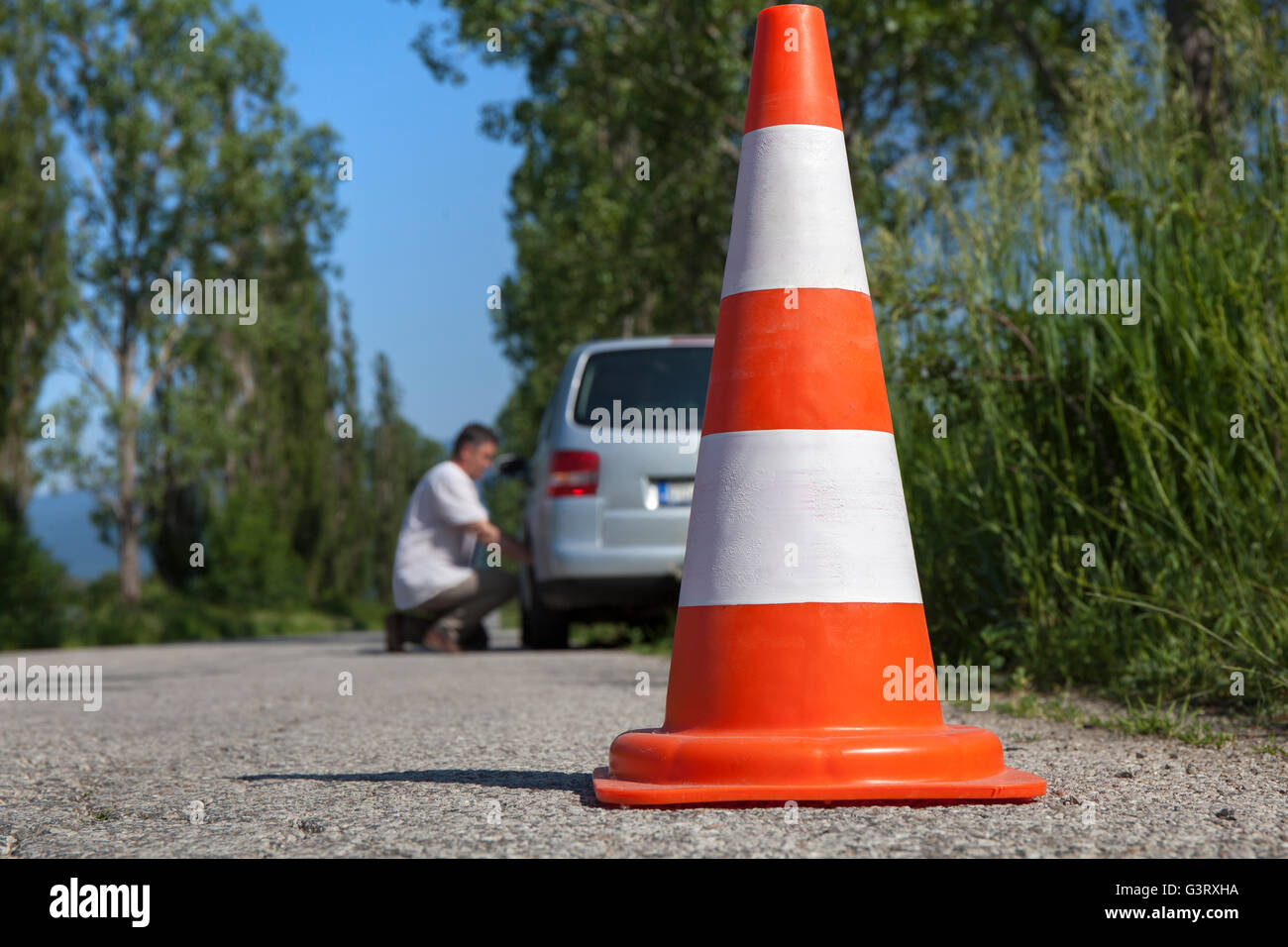 Man and car with a little breakdown on a country road. - Stock Image